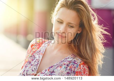 Close-up of girl in dress with floral print near building, toned photo