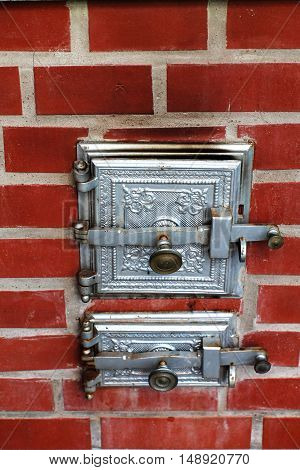 Furnace with silver  iron  doors on red brick oven wall.