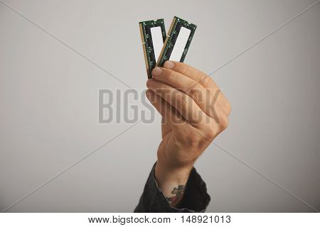 Close up of a tattooed man's hand with two RAM planks with chips against white wall background