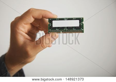 Unlabeled memory chip in a man's hand against a white wall background