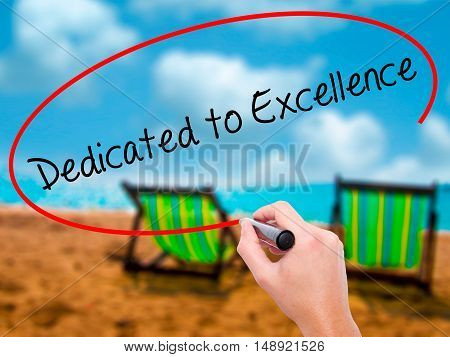 Man Hand Writing Dedicated To Excellence  With Black Marker On Visual Screen