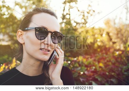 Close up portrait of a beautiful Caucasian woman having mobile phone conversation. Young female in hipster sunglasses speaks by phone while walking in autumn park.  Copy space for advertisement