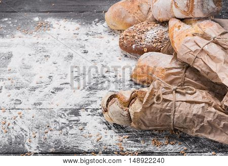 Baking and cooking concept background. Border of different bread sorts, wrapped in craft paper with copy space on wooden table, sprinkled with flour.