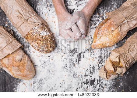 Bread making. Lots of different bread sorts, wrapped in craft paper. Baking and cooking concept background. Hardworking hands of baker on wooden table, sprinkled with flour.