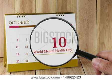 Magnifying glass in hand on calendar you can look World Mental Health Day in 10 October concept of a public relations campaign Mental health and stress.