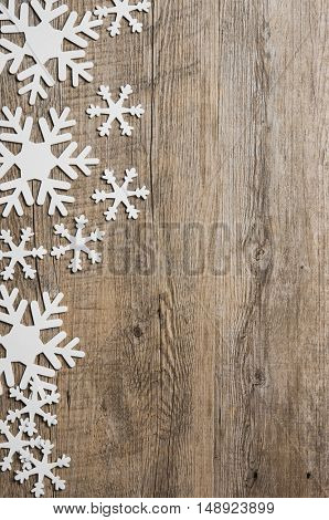 Top view of white snowflakes border on grunge wooden background with copyspace. High angle view of snowflakes, winter holidays concept.