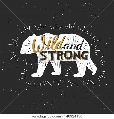 "Silhouette of a bear. Hand drawn typography poster greeting card for t-shirt design ""Wild and strong"" hand lettering quote. Vector illustration"