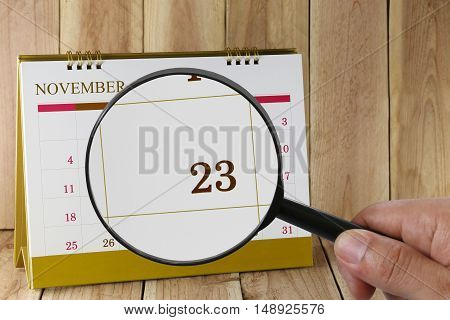 Magnifying glass in hand on calendar you can look Twenty-three days of month. Focus number Twenty-three in November. Concept in business and meetings.