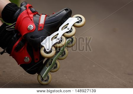 red roller blades closeup against the background of asphalt