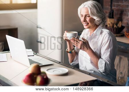 Pleasure of communication. Attractive old lady checking her e-mail at light spacious kitchen