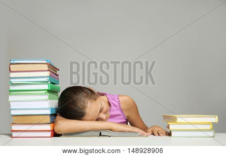 Cute girl sleeping with books on grey background
