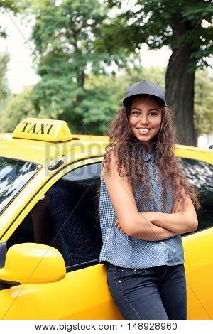 Female taxi driver near car