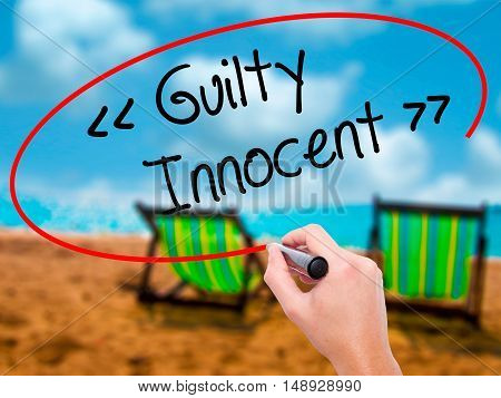 Man Hand Writing Guilty - Innocent With Black Marker On Visual Screen.