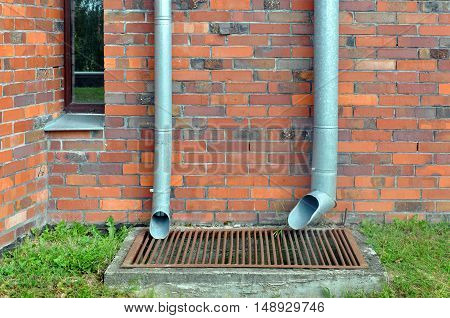 Bottom of red brick wall with metal downspout and pit.