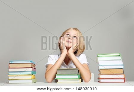 Cute girl with books on grey background