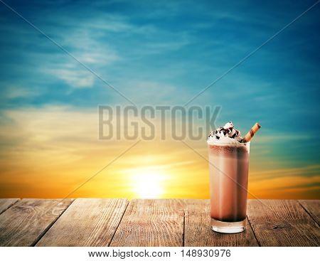 Delicious chocolate milkshake on beautiful sunset background