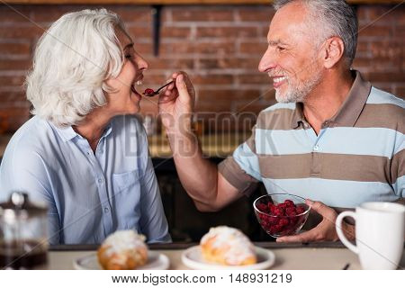 Oldies-Goldies. Elegant old couple having fun during breakfast eating raspberry