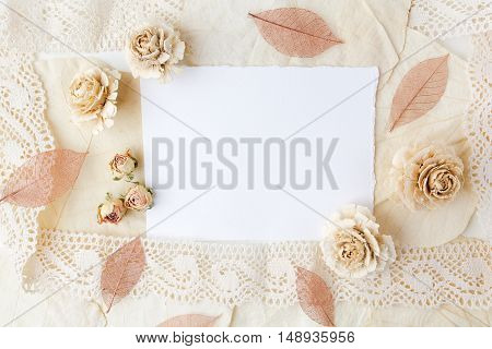 Dried biege flowers andleaves wiht blank paper. Flat lay.
