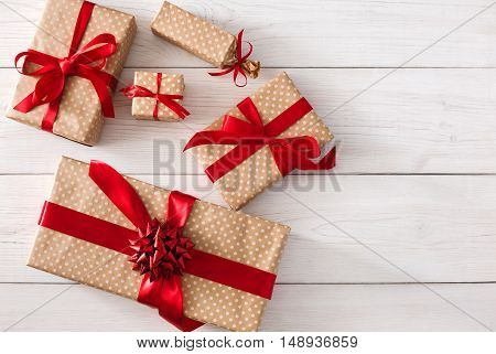 Top view of various gift boxes on white wood background. Presents in craft paper decorated with red ribbon bows. Christmas and other holidays concept, top view with copy space.