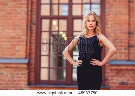 Stylish young beautiful blonde woman in elegant black dress with red lips outdoors with hand akimbo