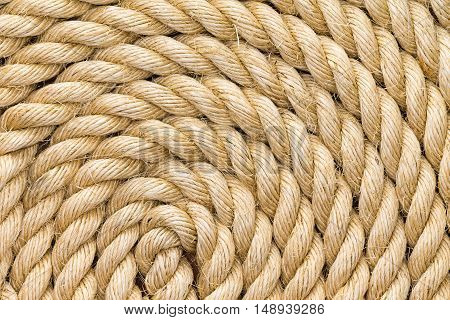 Rope background texture neatly wound into a coil showing the detail of the natural jute sisal or hemp fibers in a full frame view