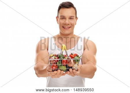 Smiling man offering a small shopping basket full of fruits and vegetables isolated on white background
