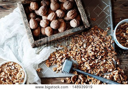 Walnut Kernels And Whole Walnuts On Rustic Old Wooden Table. Who