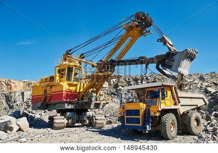 excavator loading granite or ore into dump truck at opencast