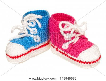 Handmade blue and pink baby booties isolated on white background