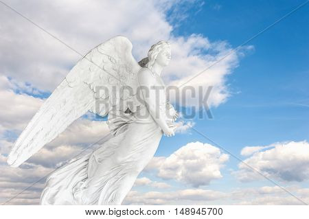 Photo montage with 150 year old Angel cemetery statue on blue sky with clouds