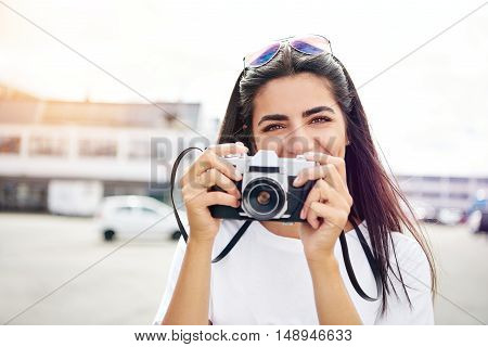 Smiling happy female tourist with a camera in her hands standing in town with her sunglasses perched on her head grinning at the camera