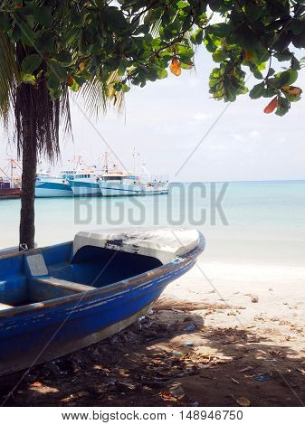panga fishing boat on shore Brig Bay Big Corn Island Nicaragua Central America with commerical fishing fleet in background in harbor