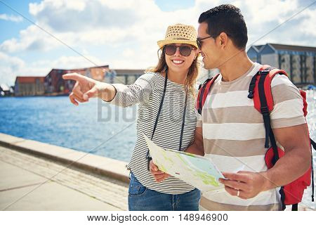 Young couple sightseeing on vacation standing holding a map on a waterfront promenade with an excited young woman pointing to something