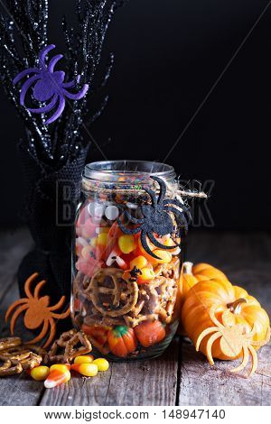 Halloween candy and snacks in a jar on dark background