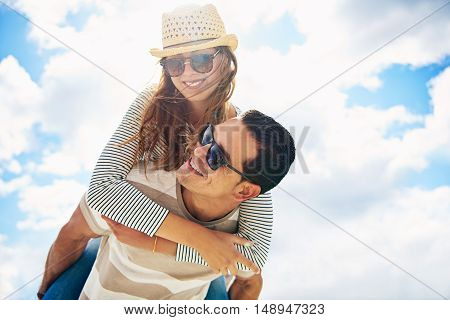 Vivacious trendy young man and woman with happy smiles having fun piggy back riding in the hot summer sun against a cloudy blue sky