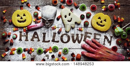 high-angle shot of a wooden table sprinkled with icing sugar where you can read the word Halloween, some different candies and cookies, and some scary ornaments, such as an amputated hand and a finger