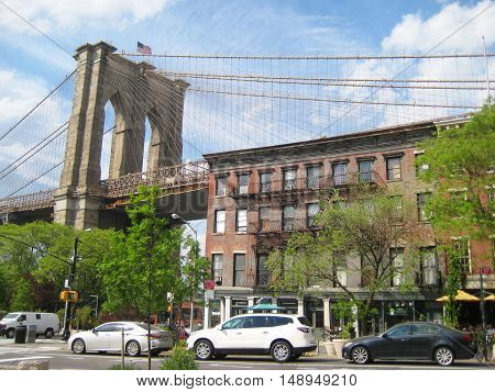 Brooklyn Bridge in New York City view from residential Brooklyn Heights luxury neighborhood area with apartment building and cars parked in front. New yorker lifestyle tourism travel concept