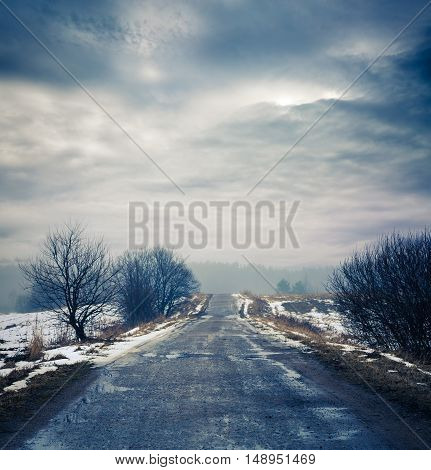 Winter Landscape. Dirty Road, Fog and Moody Sky. HDR Styled Clouds. Toned Photo with Copy Space.
