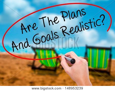 Man Hand Writing Are The Plans And Goals Realistic? With Black Marker On Visual Screen.