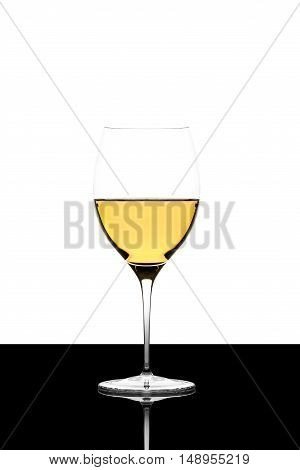 white wine glass on a black board isolated and backlit and reflection