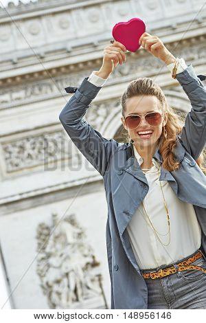 Trendy Woman Near Arc De Triomphe Showing Red Heart