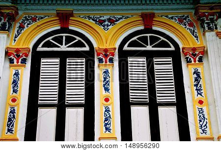 Melaka Malaysia - December 27 2007: Brightly painted pargetted plasterwork pilasters frame louvered shutter windows on an early 20th century Chinese shop house on Jalan Kaumpung Pantan