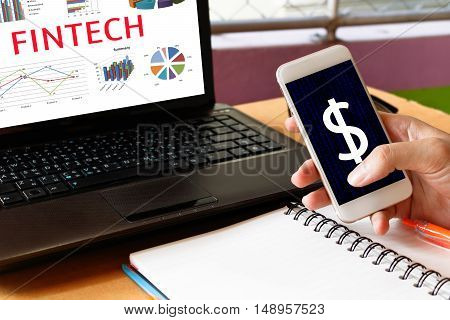 Fintech Investment Financial Internet Technology Concept. Man holding using mobile phone and graph and business technology on laptop screen.