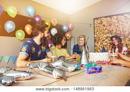 Group of four friends celebrating for a birthday party. Gifts party decorations and cake on table in front of them.
