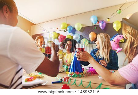 Coworkers laughing during a birthday party. Decorations made from colorful balloons on chalkboard behind them.