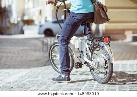 Lead an active lifestyle. Pleasant man sitting on the bike and riding it while having rest in the street