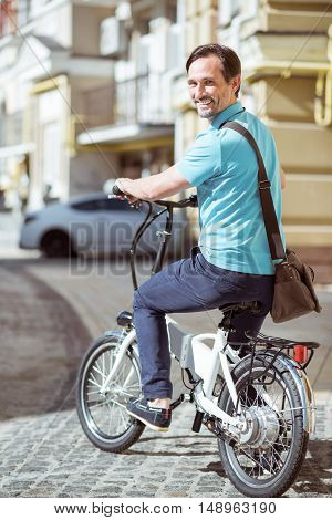 Have a nice ride. Cheerful delighted adult man smiling and riding a bicycle