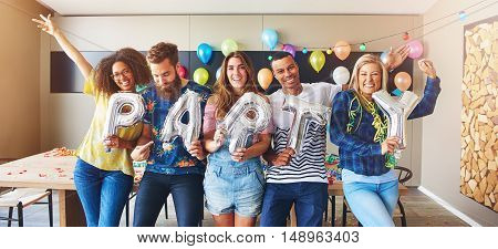 Group of friends holding balloons spelling out the word for PARTY in room with balloons in background