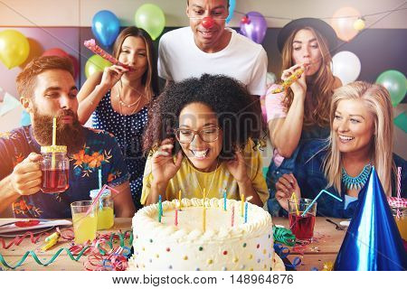 Excited woman ready to blow out candles on white frosting cake on table at birthday party with happy friends