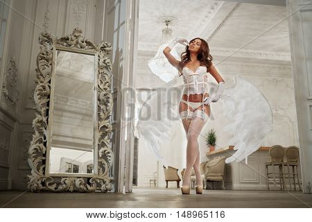 Young woman in white underwear, stockings and angel wings behind her back in room, low angle view .
